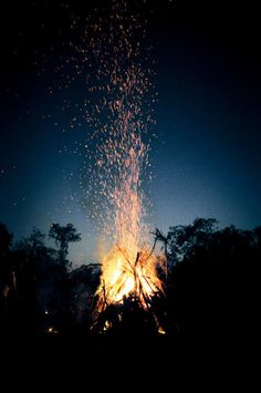 A night campfire with embers floating into the sky.