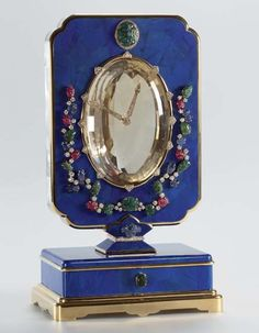 A LAPIS LAZULI AND MULTIGEM 'TUTTI FRUTTI' MYSTERY CLOCK, BY CARTIER. Maurice Coüet perfected the art of illusion in the mystery clocks that Cartier offered, beginning in 1913 based on the 'pendules mystérieuses' from the 19th century. The mechanism of these clocks is hidden in the frame such that the hands seem to float in space without any connection to the movement.