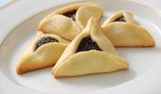 """Purim legjellegzetesebb édessége a Hámán-táska, vagy ahogy máshogy hívják """"Hámán füle'"""". A furcsa nevű édesség alakjának és elfogyasztásának több magyarázata van. Az egyik magyarázat szerint a német mák (Mohn) és a táska (Taschen) szavak összevonása, héber névelővel ellátva (Há-Mohn-Taschen), melyben így szerepel a Hámán (Há-Mohn) szó is- amely így valójában mákos táskát, vagy mákos derelyét - barátfülét jelent."""