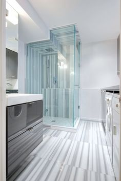 Vanity, cabinets: Ikea; laundry countertop: Perfect Stainless; floor, shower surround: Olympia Tile + Stone; showerhead: Aquabrass; shower kit: Rubi; paint: American White, Benjamin Moore