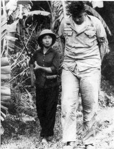 American Airman Bill Robinson being guarded by a NVA soldier following his capture on September 20, 1965 during the Vietnam War; his helicopter was shot down and the crew was taken to the Hanoi Hilton.  He became the longest-held POW in American history after spending more than seven years in captivity - he was released from the Hanoi Hilton in February of 1973.