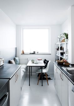 Narrow galley kitchen with a cool painted square and built in sofa. A Danish home is given a fresh, monochrome make-over. Tia Borgsmidt.