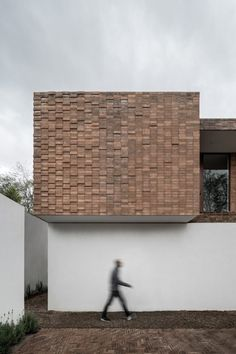 Clay bricks that clad the upper walls of the residence are stack-bonded, and protrude at different lengths to create a pixellated effect. The lower walls are made up of board-marked concrete or painted white.