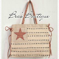 """COMING SOON! Stars & Stripes Tote COMING SOON!  This adorable bag is made of natural jute fibers with an American Flag design.  Material: Natural jute fiber, 100% cotton handles & tie backs with plastic lining Trim: 100% Cotton  Size: 18"""" W x 15.5"""" H x 4.5"""" D; Magnetic snap Mona B Bags Totes"""