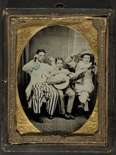 Entertainers in costume, two men and a boy with a banjo 1860