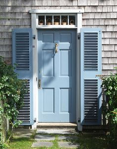 A doorway decorated with tiny lightship baskets, just outside downtown Nantucket. Blue louvered shutters.