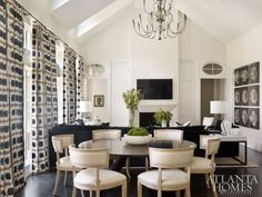 home in Atlanta designed by Melanie Turner and Jill Tompkins | boldly light & dark: light DR chairs stand out against dark background: the legs against the dark floor and the uppers against the black sofa in open concept living/dining room | photo: Emily Followill for Atlanta Homes & Lifestyles