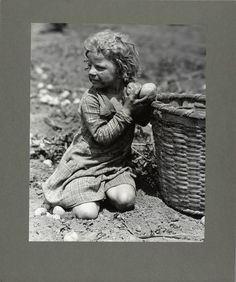 A four-year-old child helping her family pick up potatoes, 1931
