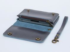The gray-blue cell phone wallet case made from genuine leather.  All process made by my hand, It 's perfectly for protect your phone. It has one pocket with mini zipper for coin, cards, cash and a slot is on top of the wallet. I add a wristlet strap on wallet for easy carrying , you can take it out as you want. The front of product has two snap buttons keep wallet close. I have many patterns for other cell phones. Please let me know if you would like this design for iPhone5, iPhone6…