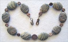 Silver Mist Jasper Necklace with Bronze by MoonbeamsLilacsRoses Miriam matched these beautiful natural stones with a handwrought, textured bronze disc focal bead, and ten matching bronze accent beads. The clasp is also handwrought and textured. As it ages, bronze develops a beautiful patina that enhances the individual character of each piece. Miriam used Old World Bronze™, which is handwrought by the Charveaux family of metalsmiths in Scottsdale, Arizona. Priced at $190.