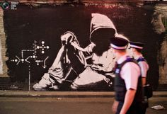 Policemen look at a mural by graffiti artist Banksy painted on the wall of a tunnel near Waterloo Station in London, June 23, 2008. A disused road tunnel in south London was turned into a giant public exhibition space by Bristol graffiti artist Banksy last month and now features murals and other work by numerous leading graffiti artists. REUTERS/Finbarr O'Reilly