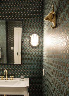 The bathroom's teal-and-gold hexagonal-patterned wallpaper adds a lively vibe to the transitional space, while a white pedestal sink adds a traditional touch. Towel hooks featuring gold bull sculptures hang on the wall, providing an eclectic, funky edge. Glamorous Bathroom, Modern Bathroom, Small Bathroom, Boho Bathroom, Chic Bathrooms, Bathroom Colors, Hexagon Wallpaper, Bold Wallpaper, Bathroom Wallpaper Funky