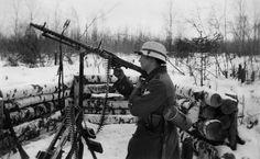 """""""Opération Barbarossa"""" de Hans Seidler Photographie mettant en scène un soldat posant avec une mitrailleuse MG34 sur affût tripode. La MG34 faisait preuve d'une grande robustesse et au cours de l'avancée en direction de Moscou, les Allemands surent en tirer le meilleur parti dans l'assaut des positions défensives russes. On note que le caporal-chef, reconnaissable à ses deux chevrons d'Obergefreiter, s'est adapté aux conditions hivernales en badigeonnant son casque avec de la peinture…"""