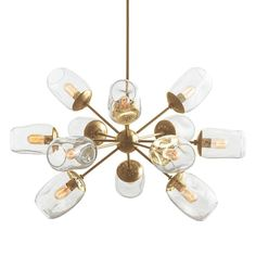This 12-light organic inspired chandelier is a creative interpretation of the ever-popular starburst motif. It is finished in antique brass and features irregularly shaped, clear seedy glass globes that house the bulbs Looks great over a dining table. Shown with vintage radio bulbs.