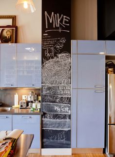 Light blue cabinets, stainless steel counters, and a chalkboard wall create a unique and beautiful kitchen! (Via Apartment Therapy)
