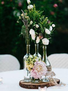 deco table mariage, style champêtre, rondin en bois, bouteilles de vin, enveloppés de ficelle en cuir, bouquet de fleurs