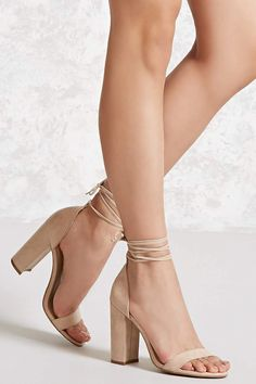 A pair of faux suede heels featuring an open toe, a wraparound self-tie closure, and a chunky heel.
