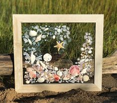 This is a handmade, one of a kind, sea glass/beach glass art piece. The picture frame measures 15.75 x 17.75. The photo represents the exact piece you will receive. Sea glass, starfish and shells are secured with a resin casting. The frame is equipped with hardware for hanging in portrait or landscape layout. Ready to ship. You will receive this exact piece. Like us on facebook- beachy decor by LV