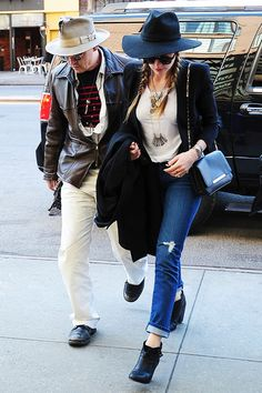 Amber Heard and Johnny Depp both wearing wide-brim hats. Amber dresses up a casual cropped distressed denim and white t-shirt combo with black ankle boots and statement jewelry.