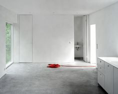 House Älta, Johannes Norlander, white plastered walls, gray concrete floor, red electrical cord