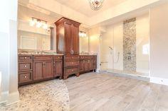 Custom Master Bathroom with custom wood like tile and large oversized shower with custom white subway tile.