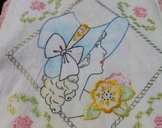 Vintage hand tinted and embroidered pillow cover of young maiden in blue bonnet