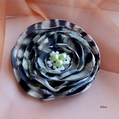 Eleanor Elegantní květ vyrobený zezlatočerné polyesterové látky. Střed brože zdobí tři zelenkavé perličky a rokajl. Průměr květu je 8 cm. Je připevněný nauniverzálním brožovém můstku, takže jde použít jak do vlasů,tak na šaty,nebo kam se vám bude líbit. Jako bonus ke každé květině dostanete zdarma skládanou origami krabičku.