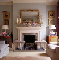 The pale blue drawing room is traditionally furnished with a club fender around the fireplace. Jane Churchill, London