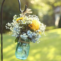 Real Weddings - In Bliss Weddings  Flowers hung from metal hangers along the ceremony aisle.