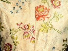 Detail fabric, caraco, mid 18th century. Cream self patterned silk brocaded with floral motifs in multicoloured silk.