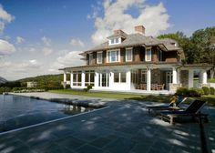 The swimming pool, stone terrace and gardens of this beautiful shingle country house in the Hudson River Valley, designed by Mackin Architects. The home is designed in the shingle-style with some colonial revival details, like the deep wraparound porch.