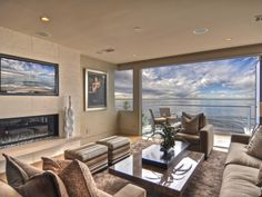 If the ocean view is the star of this contemporary living space, the room's elegant furnishings and palette are breathtaking in their supporting role. Subtle sheen on fabrics and accessories pick up the light reflecting off the water, while a floating coffee table adds whimsicality and functionality.