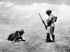 A wounded German officer, found in the Egyptian desert during the first two days of a British offensive, is guarded by a sentry while awaiting backup, on November 13, 1942.