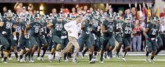 Michigan State head coach Mark Dantonio, center, leads his team onto the field. (Michael Conroy/AP)