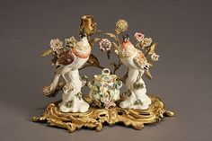 <b>Louis XV Style Porcelain and Ormolu Encrier</b> <br /> <i>Circa 1900</i> <br /> The rococo style ormolu stand centered by a porcelain covered inkwell flanked by two figures of pheasants, below porcelain flowers and an ormolu candle socket. <i>Pheasants detached from base; restorations to lid of inkwell.</i> <br /> <i>Height: 7-1/2 in (19 cm); Length: 11-1/2 in (29.2 cm)</i>Property of Various Owners <br /> <br />