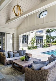 Beautiful indoor-outdoor living room design with classic wicker furniture, blue accent pillows and a modern brass chandelier.