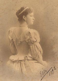 """Grã-duquesa Elizabeth Feodorovna em 1892. Ela é fotografada por trás e está olhando para a direita. Ela está usando um vestido com uma gola de renda e tem fios de pérolas e diamantes em seu cabelo e em torno de seu pescoço. A fotografia é assinada e datada """"Ella 1892 'no canto inferior direito."""