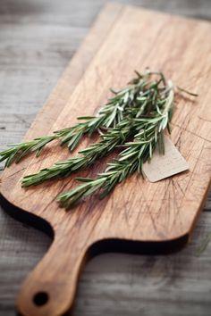 Fresh herbs. Well used cutting board.