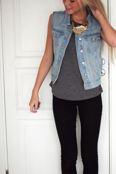 Aurora Mohn in a grey t-shirt, denim vest, gold necklace and black skinny jeans.