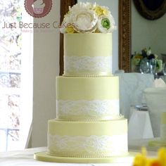 Yellow and white wedding cake with floral sugar flower topper