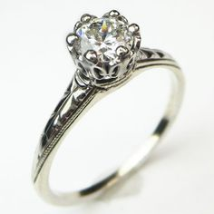 Carved Solitaire: An especially bright white diamond dazzles in a gracefully detailed crown setting, and the slender shank is adorned with sweeping sculpted lines that create movement as light plays over the surface. Ca.1940. Maloys.com