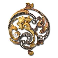 Art Nouveau floral motif flowing circular pin with a mellow patina of Antique silver over 18K yellow gold set with rose cut diamonds and a .40 carat European cut diamond amidst the whiplash foliate motif and central characteristic Art Nouveau flower.