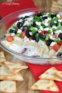 Layered Greek Dip: be whisked away to the Mediterranean with this bright, fresh, and delicious dip! Make it ahead of time and be ready to serve when your party guests arrive.