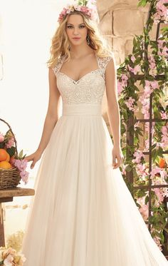 Do a graceful walk in Voyage by Mori Lee 6803. This wedding gown offers a Queen Anne neckline with delicate embroidery over soft net cover the stylish cap sleeves and extends through the back. Wide band of soft ruching encircle the waist to fit and flatter your silhouette. The full length skirt flares out to a flattering hemline and leads a majestic train.