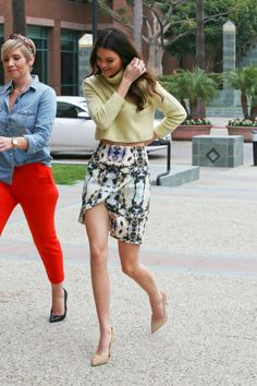 Kendall Jenner wearing a trendy yellow cut off sweater and a print mini skirt.