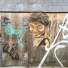 A graffiti portrait by LMNOPI on a wooden surface has a more subtle approach, the colors blending seamlessly into the wall.