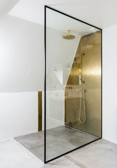 Glass & gold bathroom featuring concrete floor, curbless shower & linear drain. #artdeco