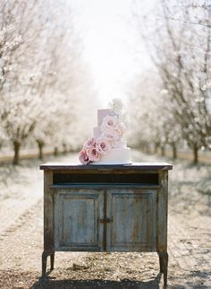 oh I love this!  how I miss pale pink blossom...vintage furniture with a weathered look for a wedding setting  glamorous wedding shoot, almond orchard wedding shoot, Claire Pettibone, pink ombre dress, lavender cake, pastel, cherry blossoms, horse, feathers, hair pieces, lace, ombre flowers, Pacific Weddings mangazine