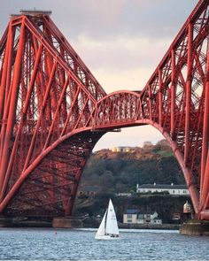 A yacht passing under the Forth Rail Bridge in Edinburgh.