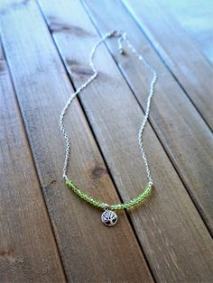 Handmade / Handcrafted Artisan Jewelry and Necklaces.  Delicate and elegant in its simplicity, this lovely necklace presents a quiet brilliance. The symbol of the tree of life has many interpretations but at its core represents the interconnected of life. The gemstone peridot is said to heal relationships as well as promote abundance and prosperity. A lovely expression of healing for humanity.